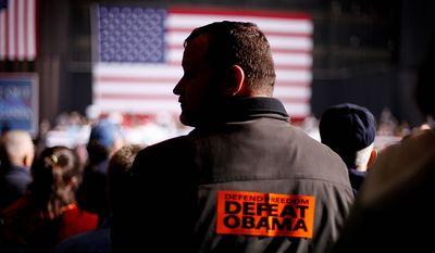 "Bill McCoy of Virginia Beach, Va., wears a ""Defeat Obama"" sticker on his back as he listens to Republican presidential candidate, former Massachusetts Gov. Mitt Romney speak during a campaign event at Farm Bureau Live, Thursday, Nov. 1, 2012, in Virginia Beach, Va. (AP Photo/David Goldman)"