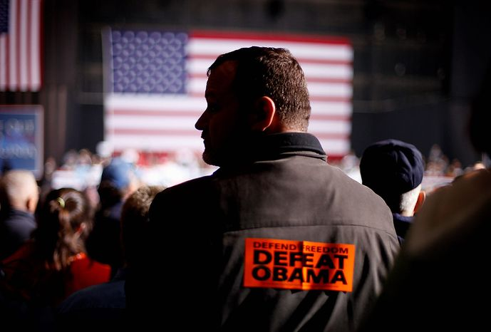 "Bill McCoy of Virginia Beach, Va., wears a ""Defeat Obama"" sticker on his back as he listens to Republican presidential candidate, former Massachusetts Gov. Mitt Romney speak during a campaign event at Farm Bureau Live, Thursday, Nov. 1, 2012, in Virginia Beach, Va. (AP Photo/David Goldman)"