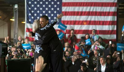 President Barack Obama is hugged by Judith Kamalay as he arrives to speak at a campaign event at the Franklin County Fairgrounds, Friday, Nov. 2, 2012, in Hilliard, Ohio, before heading to another campaign stop in in Springfield, Ohio. (AP Photo/Carolyn Kaster)