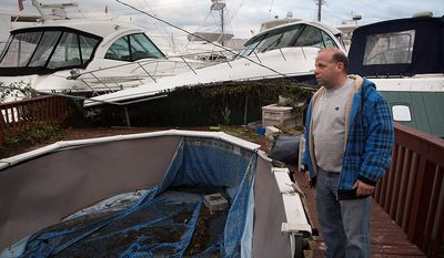 Mike Cappucci, 46, of Staten Island, surveys the damage to his home after boats from a nearby harbor were driven inland by floodwaters, Wednesday, Oct. 31, 2012, in the Staten Island borough of New York. Sandy, the storm that made landfall Monday, caused multiple fatalities, halted mass transit and cut power to more than 6 million homes and businesses. (AP Photo/ John Minchillo)