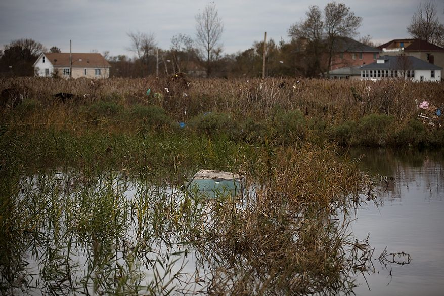 A vehicle is submerged after being carried into a swampy depression by floodwaters, Wednesday, Oct. 31, 2012, in the Staten Island borough of New York. Sandy, the storm that made landfall Monday, caused multiple fatalities, halted mass transit and cut power to more than 6 million homes and businesses. (AP Photo/ John Minchillo)