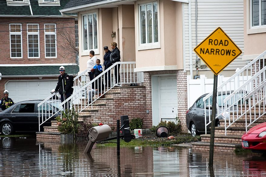 Rescue workers check a home for fuel leaks and other types of damage, Wednesday, Oct. 31, 2012, in the Staten Island borough of New York. Sandy, the storm that made landfall Monday, caused multiple fatalities, halted mass transit and cut power to more than 6 million homes and businesses. (AP Photo/ John Minchillo)