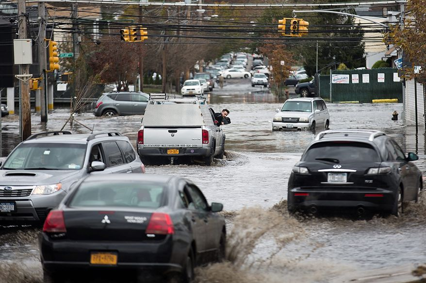 A passenger inspects the water level around his vehicle as multiple cars drive through  a flooded street, Wednesday, Oct. 31, 2012, in the Staten Island borough of New York. Sandy, the storm that made landfall Monday, caused multiple fatalities, halted mass transit and cut power to more than 6 million homes and businesses. (AP Photo/ John Minchillo)
