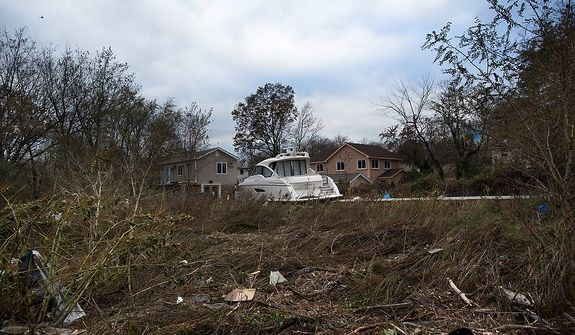 A yacht rests beside two homes after it was driven inland by flood waters, Wednesday, Oct. 31, 2012, in the Staten Island borough of New York. Sandy, the storm that made landfall Monday, caused multiple fatalities, halted mass transit and cut power to more than 6 million homes and businesses.(AP Photo/ John Minchillo)