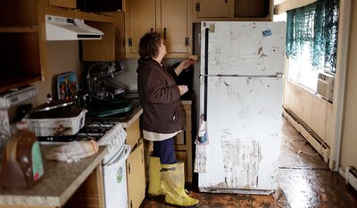 Eileen Miley looks for magnets that might be salvageable at her home that was destroyed by flooding during Superstorm Sandy in Staten Island, New York, Thursday, Nov. 1, 2012. The National Guard and federal emergency management officials will deliver 1 million meals and bottled water to New York areas hardest hit by Superstorm Sandy.  (AP Photo/Seth Wenig)