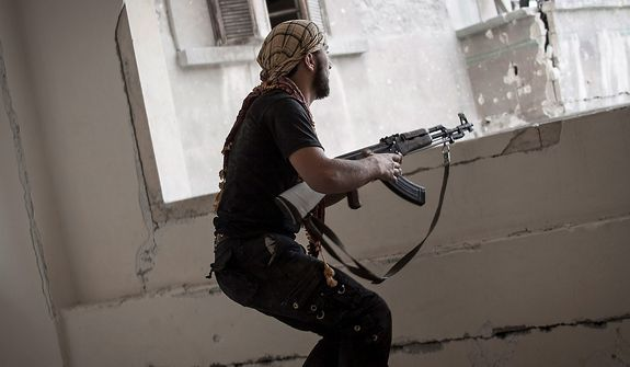 In this Wednesday, Oct. 31, 2012 photo, a rebel fighter prepares to fire on pro-government forces in the Karm al-Jebel neighborhood of Aleppo, Syria. Violent clashes re-ignited along the city's frontline while government warplanes attacked rebel controlled areas throughout the financial capital of Syria's largest city. (AP Photo/Narciso Contreras).