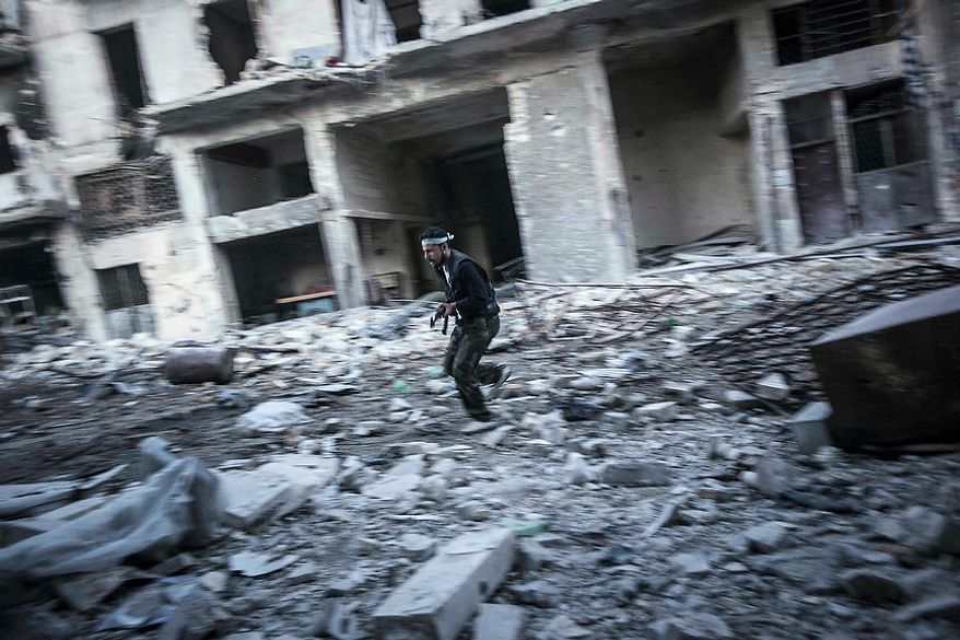 In this Thursday, Nov. 1, 2012 photo, a rebel fighter runs for cover at the front line during clashes in the Karmal Jabl battlefield in Aleppo, Syria. (AP Photo/Narciso Contreras)
