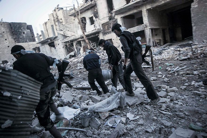 In this Thursday, Nov. 1, 2012 photo, rebel fighters carry out a bomb through the front line streets as they prepare an attack against Syrian army troops during clashes in the Karmal Jabl battlefield in Aleppo, Syria. (AP Photo/Narciso Contreras)