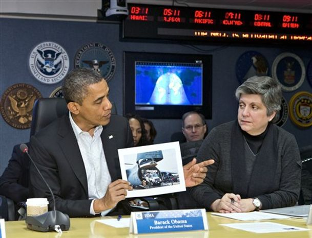 President Barack Obama visits the Federal Emergency Management Agency (FEMA) for an update on the recovery from Hurricane Sandy that hit New York and New Jersey especially hard as well as much of the East Coast earlier this week, Saturday morning, Nov. 3, 2012, in Washington. He is joined by Homeland Security Secretary Janet Napolitano, right, as he displays a photo of an Air Force C-17 transporting utility trucks to aid the devastated areas. (AP Photo/J. Scott Applewhite)