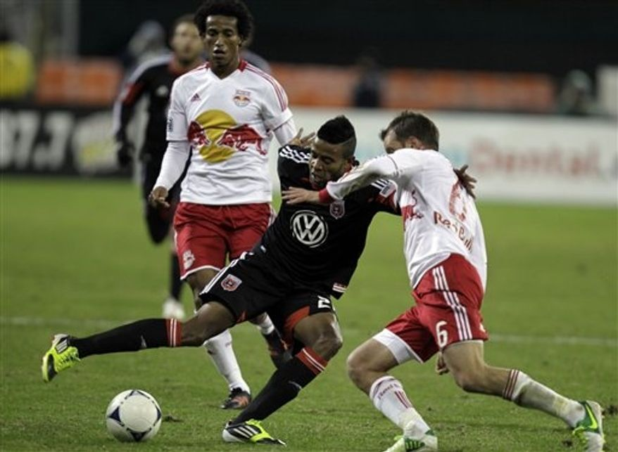 D.C. United's Lionard Pajoy, center, moves the ball as New York Red Bulls' Roy Miller, left, and Teemu Tainio (6) defend during the second half in Game 1 of an MLS soccer Eastern Conference semifinal playoff series on Saturday, Nov. 3, 2012, in Washington. The game ended in a 1-1 tie. (AP Photo/Luis M. Alvarez)