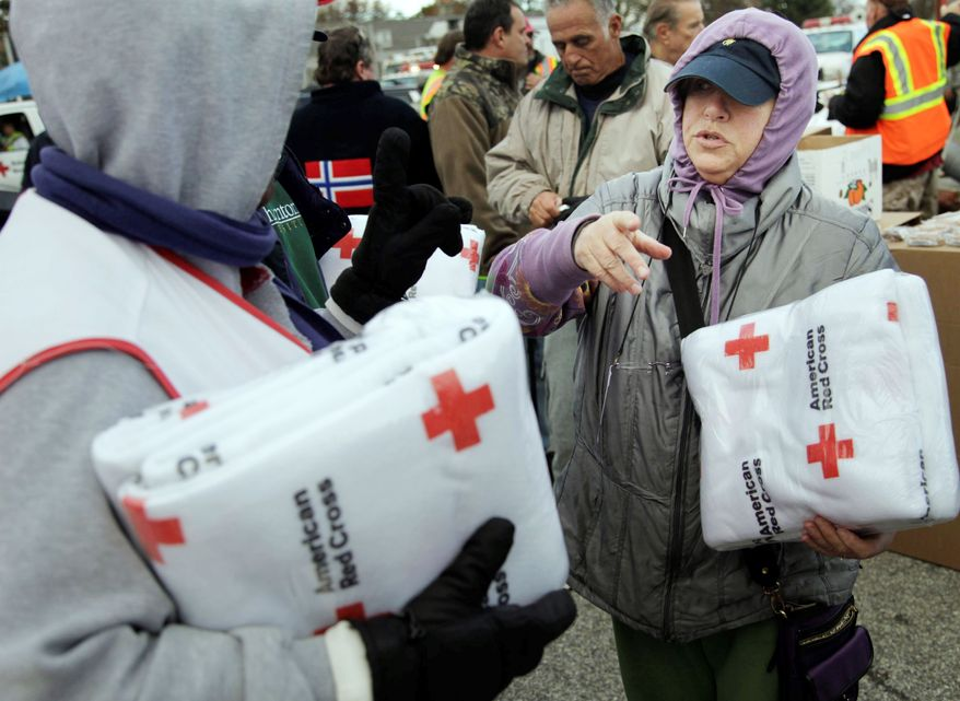 Galina Quacinella (right) gets some blankets for herself and her husband at a Red Cross aid station on Staten Island. Overnight temperatures are sinking into the 30s. The city has opened warming centers in senior centers and set up food distribution sites. (Associated Press)