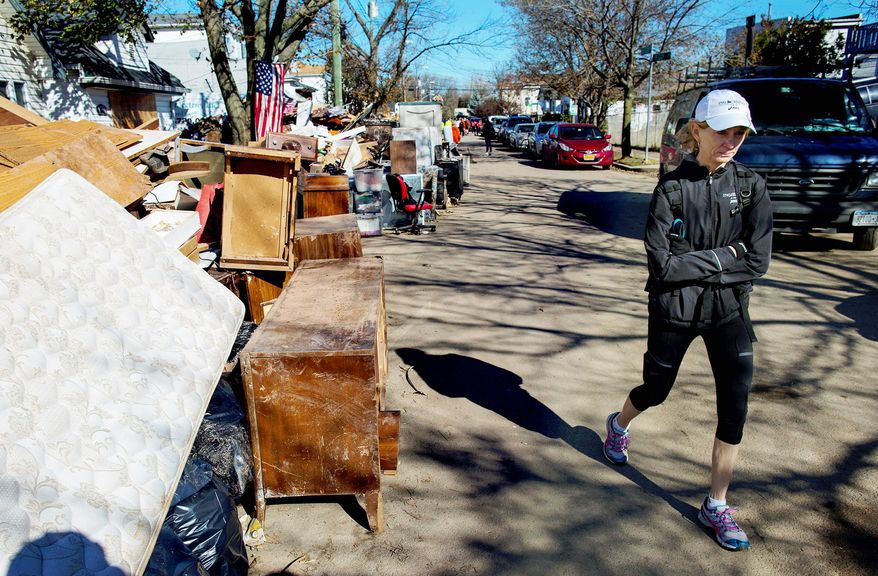 Mary Wittenberg, president of the New York Road Runners, walks down a street lined with furniture and other belongings after speaking Sunday with a family on Staten Island whose house was heavily damaged during Superstorm Sandy. With the cancellation of the New York Marathon, hundreds of runners, carrying backpacks full of supplies, took the ferry to the hard-hit island to help people in neighborhoods. (Associated Press)