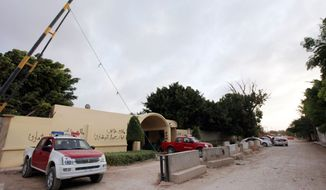 Libyan investigators' cars park in front of the U.S. Consulate in Benghazi after the Sept. 11 the attack that killed four Americans, including Ambassador J. Christopher Stevens. The commander of U.S. operations in Africa and officials at the Pentagon agreed that the picture on the ground was too clouded to order an airstrike. (Associated Press)