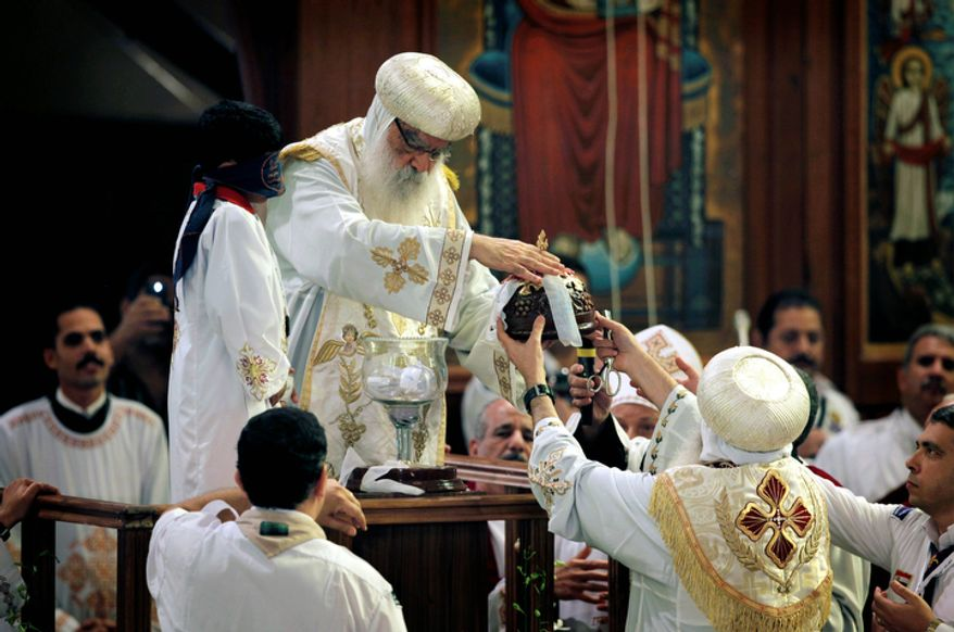 Coptic Pope Pachomios unseals the crystal chalice containing balls with the candidates names during the papal election ceremony at the Coptic Cathedral in Cairo, Egypt, Sunday, Nov. 4, 2012. Egypt's ancient Coptic Christian church chose a new pope in an elaborate Sunday ceremony meant to invoke the will of God, in which a blindfolded boy drew the name of the next patriarch from a crystal chalice. Bishop Tawadros will be ordained Nov. 18 as Pope Tawadros II, the spiritual leader of a community that increasingly fears for its future amid the rise of Islamists to power in the wake of the 2011 ouster of longtime authoritarian leader Hosni Mubarak.(AP Photo/Nasser Nasser)