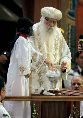 A blindfolded boy waits to draw the name of the next patriarch from a crystal chalice while acting Coptic Pope Pachomios mixes the balls with the candidates names during the papal election ceremony at the Coptic Cathedral in Cairo, Egypt, Sunday, Nov. 4, 2012. Bishop Tawadros will be ordained Nov. 18 as Pope Tawadros II.  (AP Photo/Nasser Nasser)