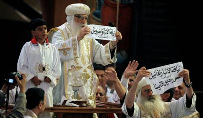Acting Coptic Pope Pachomios, center, displays the name of 60-year-old Bishop Tawadros, soon to be Pope Tawadros II, while another clergyman displays the names of the remaining two candidates, Bishop Raphael and Father Raphael Ava Mina, during the papal election ceremony at the Coptic Cathedral in Cairo, Egypt, Sunday, Nov. 4, 2012.   (AP Photo/Nasser Nasser)