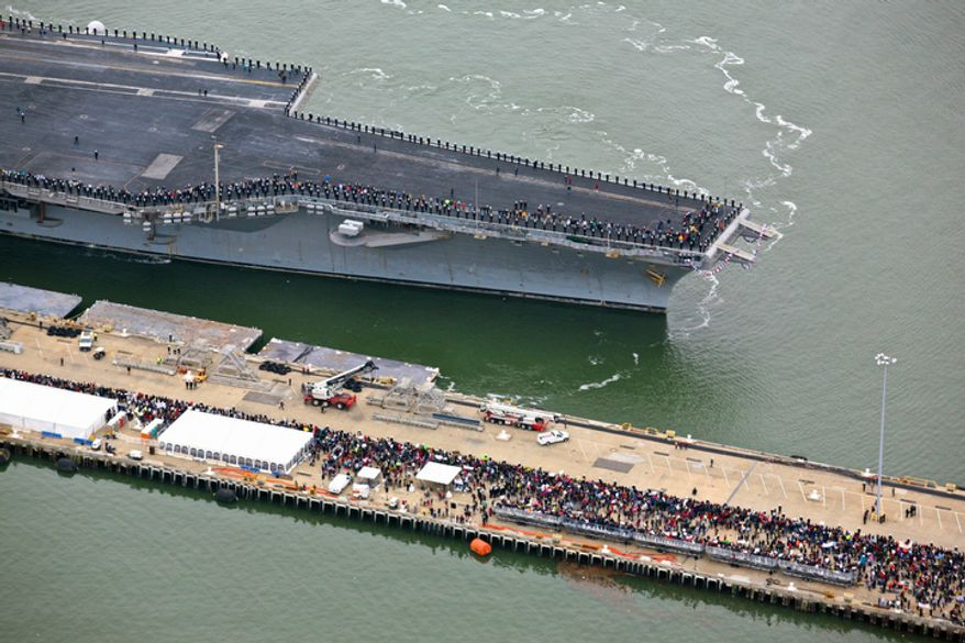 The USS Enterprise, the world's first nuclear-powered aircraft carrier, pulls into the dock at Norfolk Naval Station. The USS Enterprise began shutting down its eight nuclear reactors almost as soon as it arrived at its pier, where thousands of cheering family members and friends welcomed the ship home from its 25th and final deployment after nearly eight months at sea. (AP Photo/The Virginian-Pilot,  Randall Greenwell)