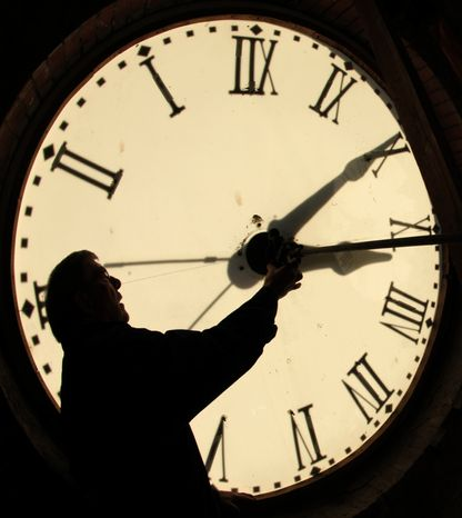 ** FILE ** Custodian Ray Keen checks the clock face after changing the time on the 97-year-old clock atop the Clay County Courthouse on Nov. 6, 2010, in Clay Center, Kan. (AP Photo/Charlie Riedel)