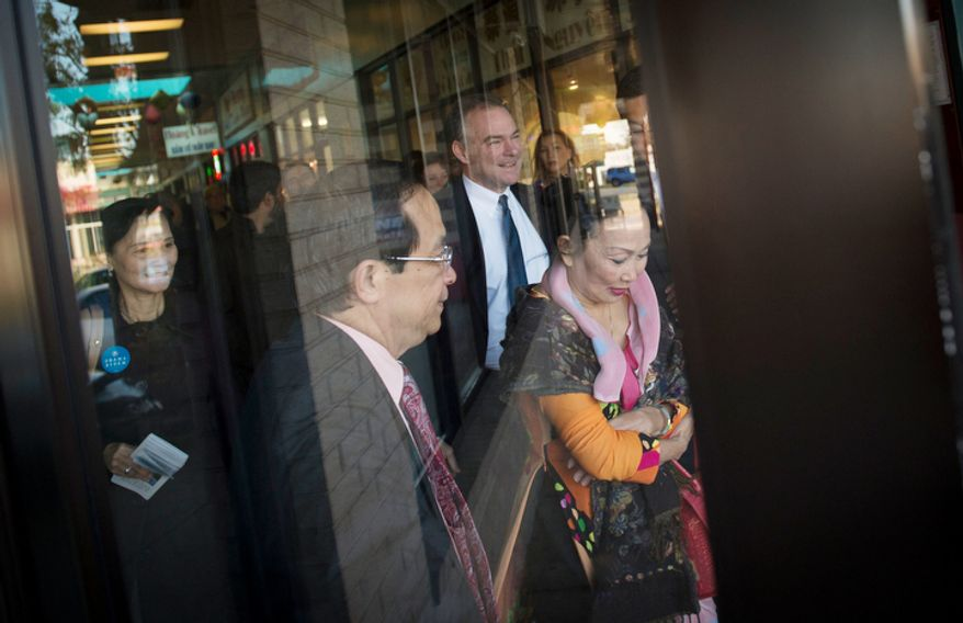 Democratic U.S. Senate candidate and former Virginia Governor Tim Kaine (center) is joined by Anh Hong Do (left) and Kim-Ha Ly (right) as he arrives to meet customers and business owners at Eden Center in Falls Church, Va. (Rod Lamkey Jr./The Washington Times)