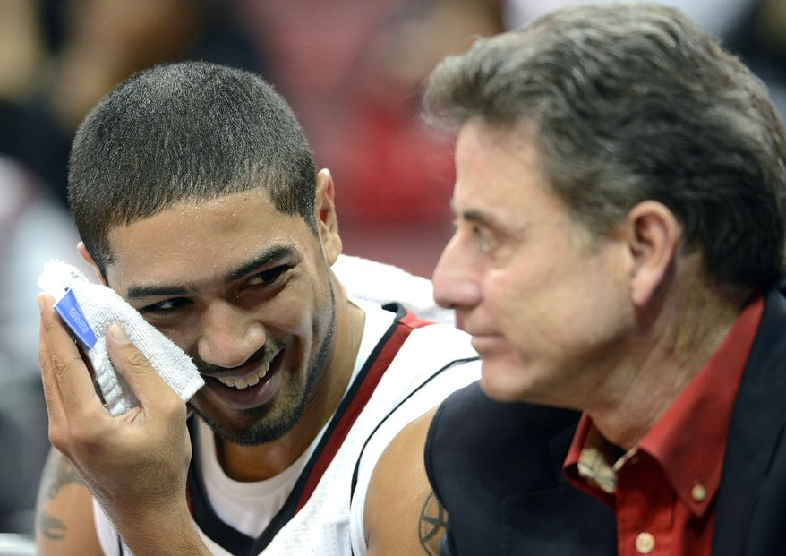 Louisville's Peyton Siva, left, shares a laugh with head coach Rick Pitino during their intrasquad NCAA college basketball scrimmage, Saturday, Oct. 27, 2012 at the KFC Yum! Center in Louisville, Ky. (AP Photo/Timothy D. Easley)