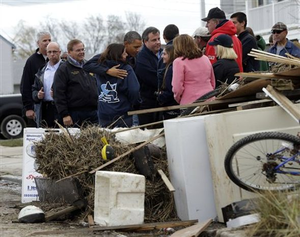President Obama, center, and and Gov. Chris Christie meet with local residents as they tour neighborhood effected by superstorm Sandy, Wednesday, Oct. 31, 2012 in Brigantine, N.J. (AP Photo/Pablo Martinez Monsivais)