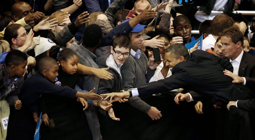 President Barack Obama extends his arm and fingers to greet young supporters after speaking at a campaign event at Fifth Third Arena, Sunday, Nov. 4, 2012, in Cincinnati. (AP Photo/Pablo Martinez Monsivais)