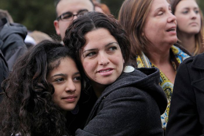 Romina Moreno, center, holds her daughter Natalie Pena, 12, left, to stay warm while waiting for former President Bill Clinton to arrive at Pullen Park in Raleigh, N.C., to speak at a rally for Barack Obama on Sunday, Nov. 4, 2012.  The former president has been traveling to several battleground states over the past week to try to stem any Republican tide for Mitt Romney and preserve Obama leads. (AP/Ted Richardson)