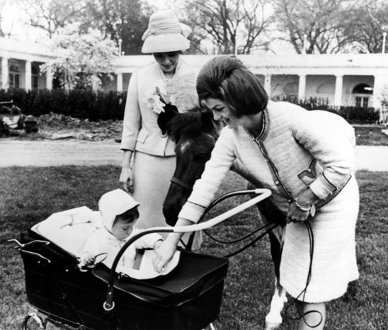 Empress Farah of Iran and Mrs. Jacqueline Kennedy pause on a tour of the White House south grounds, Washington, today, April 12, 1962, to visit with John F. Kennedy, Jr., year and a half old son of the President and Mrs. Kennedy. Macaroni, Caroline Kennedy's pony, has the freedom of the grounds and chimes in. (AP-PHOTO/pl)