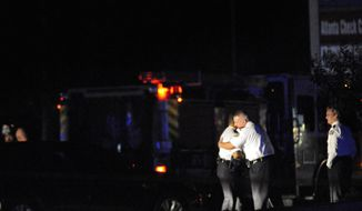 **FILE** Law enforcement officers console each other Nov. 4, 2012, as others investigate the scene of an Atlanta Police Department helicopter crash that killed two officers aboard the chopper when it crashed near a shopping center late Saturday, Nov. 3, 2012. (Associated Press)