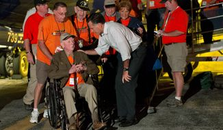 **FILE** Republican presidential candidate Mitt Romney shakes hands in Swanton, Ohio, with World War II and Korean War veterans returning on an Honor Flight from Washington on Sept. 26, 2012. (Associated Press)