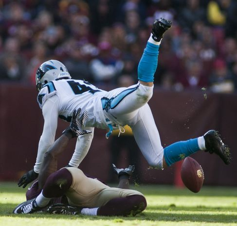 Carolina Panthers free safety Haruki Nakamura (43) hits Washington Redskins wide receiver Josh Morgan (15) in the head resulting in a fifteen yard personal foul in the second quarter, Landover, Md., Sunday, November 4, 2012.  (Craig Bisacre/The Washington Times)
