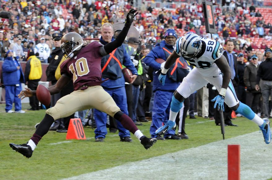 Washington Redskins quarterback Robert Griffin III (10) is knocked out of bounds late in the game by Carolina Panthers outside linebacker Thomas Davis (58), who was called for a late hit on the play at FedEx Field, Landover, Md., Nov. 4, 2012. (Preston Keres/Special to The Washington Times)