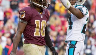 Carolina Panthers defensive back Josh Norman (24) points to the scoreboard after Washington Redskins quarterback Robert Griffin III (10) scores on a 3 yard run late in the fourth quarter as the Washington Redskins take on the Carolina Panthers at FedEx Field, Landover, Md., Sunday, November 4, 2012. The touchdown would be called back on an offensive holding play. (Andrew Harnik/The Washington Times)