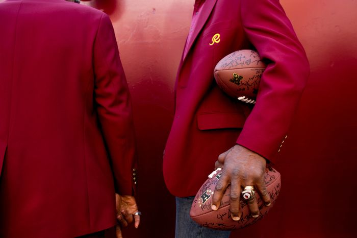 Former Washington Redskins punt returner Mike Nelms, right, who played with the Redskins for five seasons from 1980-1984 holds signed footballs as he and other former Washington Redskins players take the field as part of the annual Washington Redskins Homecoming festivities before the Washington Redskins take on the Carolina Panthers at FedEx Field, Landover, Md., Sunday, November 4, 2012.(Andrew Harnik/The Washington Times)