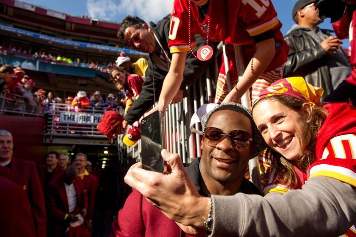"Former Washington Redskins running back Clinton Portis, takes a photo with Bernice Cohen of Silver Spring, Md., as he makes his way out of the tunnel during for the annual Washington Redskins Homecoming festivities before the Washington Redskins take on the Carolina Panthers at FedEx Field, Landover, Md., Sunday, November 4, 2012. Portis is one of the ""10 for 80"" honorees selected to be added to the 70 greatest former players as part of the 80th anniversary of the Washington Redskins. (Andrew Harnik/The Washington Times)"