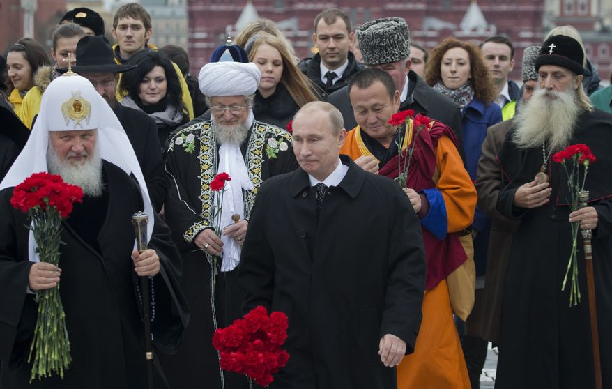 Russian President Vladimir Putin (center) walks with religious leaders of various denominations at Red Square in Moscow as they go to place flowers at a statue of Minin and Pozharsky, the leaders of a struggle against foreign invaders in 1612, to mark the National Unity Day on Sunday, Nov. 4, 2012. (AP Photo/Misha Japaridze)