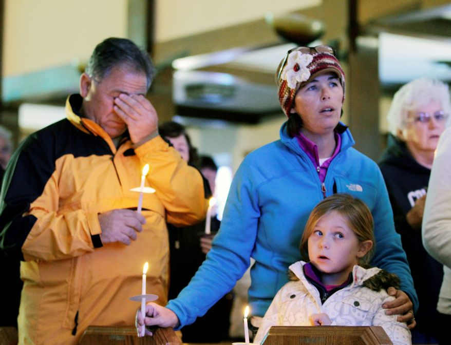 A man wipes his eyes as he, Kathleen Beissel and her daughter Meaghan, 7, attend Sunday mass at the St. Thomas More Catholic church in Breezy Point, in the wake of Superstorm Sandy, Sunday, Nov. 4, 2012, in New York.  (AP Photo/Kathy Willens)