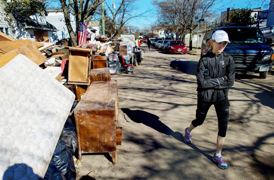 Mary Wittenberg, president of the New York Road Runners, reacts after viewing areas heavily damaged during Superstorm Sandy, in the Staten Island borough New York, Sunday, Nov. 4, 2012. With the cancellation of the New York Marathon, hundreds of  runners, wearing their marathon shirts and backpacks full of supplies, took the ferry to hard-hit Staten Island and ran to hard-hit neighborhoods to help.  (AP Photo/Craig Ruttle)