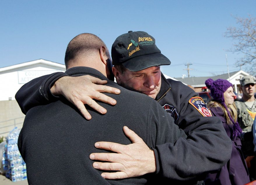 """New York Fire Department Marine Ops Batallion Chief James Dalton, right, who is in charge of """"dewatering,"""" embraces a colleague after losing his composure while giving instructions to dozens of New York Cares volunteers who came to the area for the day to help in Breezy Point, in the wake of Superstorm Sandy, Sunday, Nov. 4, 2012, in New York.  (AP Photo/Kathy Willens)"""