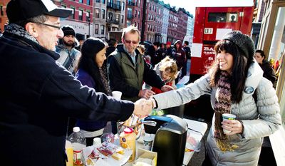 Felice Vazquez, 40, of Hoboken, greets a neighbor as she mans a table providing hot drinks and snacks on Washington Street as the buildings around them remain without power due to damage caused by Superstorm Sandy, Sunday, Nov. 4, 2012, in Hoboken, New Jersey.  (AP Photo/ John Minchillo)