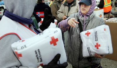 Galina Quacinella, right, gets some blankets for herself and her husband at a Red Cross aid station in Staten Island, New York, Sunday, Nov. 4, 2012. With overnight temperatures sinking into the 30s, hundreds of thousands of homes and businesses are still without electricity in the aftermath of Superstorm Sandy. (AP Photo/Seth Wenig)