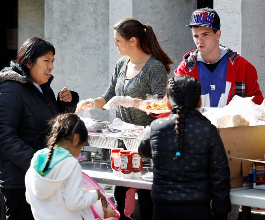 Enriqueta Gil watches as her daughters, eight-year-old Diana Gil-Velasco, right, six-year-old Elizabeth Gil-Velasco, second left, are served donated hot meals by volunteers  Sunday, Nov. 4, 2012, outside the Belmar recreation center in Belmar, N.J. After being battered by Monday's storm surge by Superstorm Sandy much of the region is still without power and many homes have been damaged. (AP Photo/Mel Evans)
