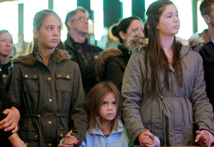 Girls hold hands during Sunday mass at St. Thomas More Catholic Church in Breezy Point, in the wake of Superstorm Sandy, Sunday, Nov. 4, 2012, in New York. (AP Photo/Kathy Willens)