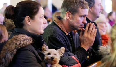 """Meg Dolan holds her dog """"Nellie"""" during Sunday mass at St. Thomas More Catholic Church in Breezy Point, in the wake of Superstorm Sandy, Sunday, Nov. 4, 2012, in New York. (AP Photo/Kathy Willens)"""