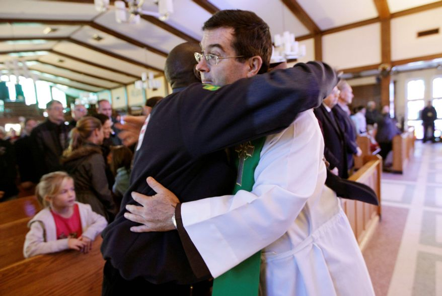 The Rev. Brian Jordan, right, embraces New York State Senator Malcolm Brown after Sunday mass at St. Thomas More Catholic Church in Breezy Point, Sunday, Nov. 4, 2012, in New York. Breezy Point, the beachfront enclave heavy populated by firefighters and police officers was devastated during the storm when a fire pushed by Sandy's raging winds destroyed 100 or more homes and buildings.  (AP Photo/Kathy Willens)