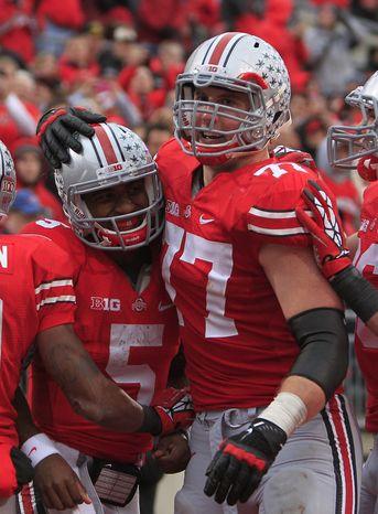 Ohio State quarterback Braxton Miller (left) celebrates his touchdown against Illinois with teammate Reid Fragel during the third quarter of Ohio State's 52-22 win over Illinois on Nov. 3, 2012, in Columbus, Ohio. (Associated Press)