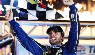 Jimmie Johnson (48) celebrates with the checkered flag in victory lane following his win in the NASCAR Sprint Cup Series auto race at Texas Motor Speedway, Sunday, Nov. 4, 2012, in Fort Worth, Texas. (AP Photo/Tony Gutierrez)