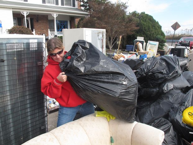 Laura DiPasquale sorts through bags of possessions that volunteers removed from her home in Point Pleasant Beach, N.J., on Monday, Nov. 5, 2012. (AP Photo/Wayne Parry)