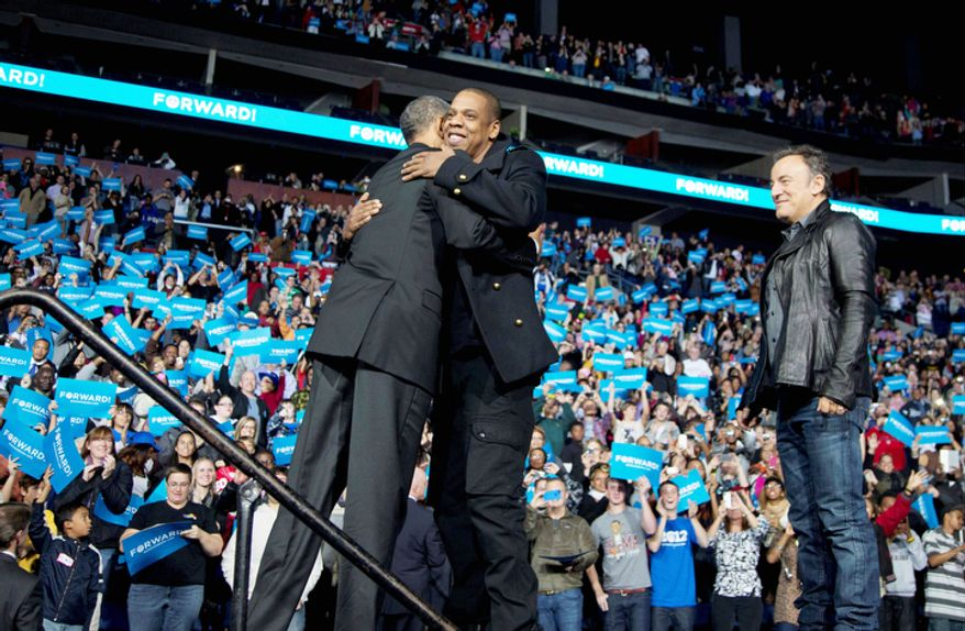 President Barack Obama is hugged on stage by musician Jay-Z, center, as musician Bruce Springsteen, stands right, at a campaign event at Nationwide Arena, Monday, Nov. 5, 2012, in Columbus, Ohio.  (AP Photo/Carolyn Kaster)