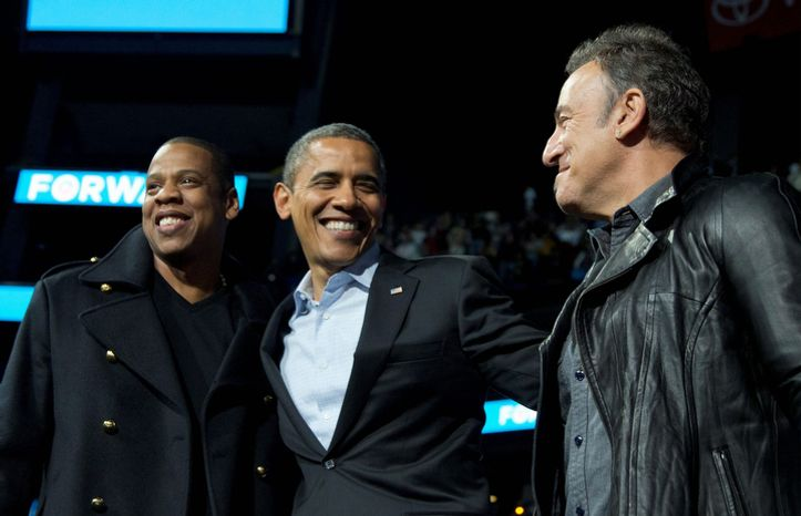 President Barack Obama is flanked on stage by musicians Jay-Z, left, and Bruce Springsteen at a campaign event at Nationwide Arena, Monday, Nov. 5, 2012, in Columbus, Ohio.  (AP Photo/Carolyn Kaster)